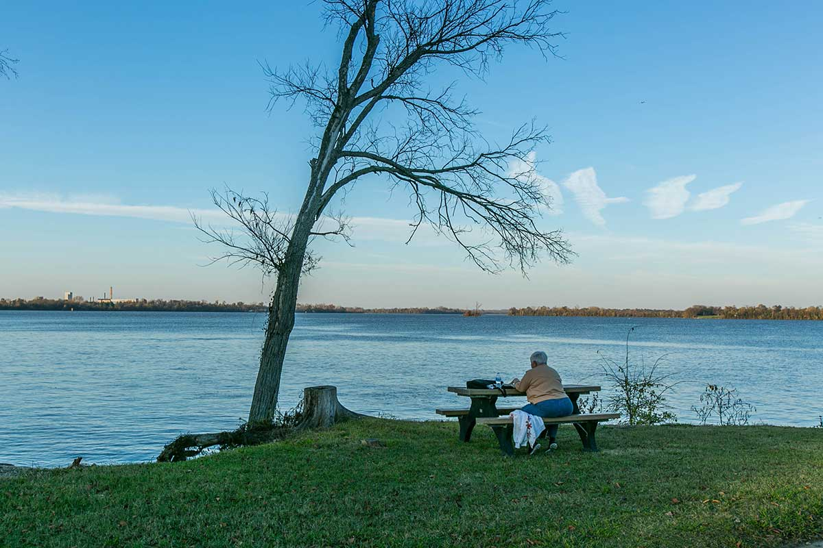 Person sitting on bench in front of water in Hopewell, VA