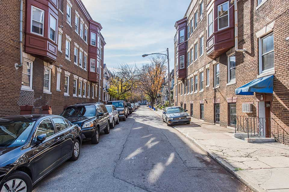 Street with cars and apartments in Spruce Hill, Philadelphia, PA